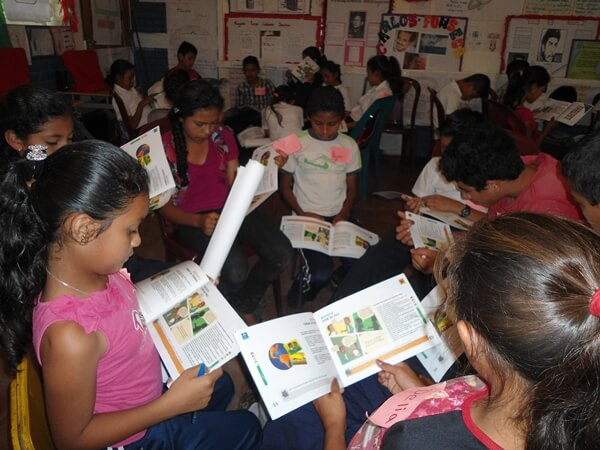 Niños leyendo documento ODS
